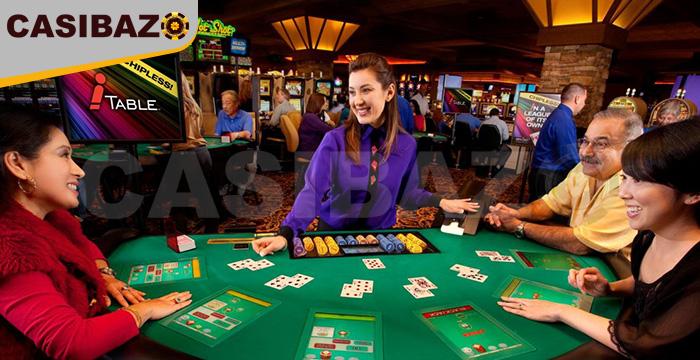 افراد سر میز قمار در یک کازینو نشسته اند